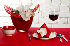 Table setting with orchid flowers. Table setting with white orchid flowers on red tablecloth on brick wall background royalty free stock photo