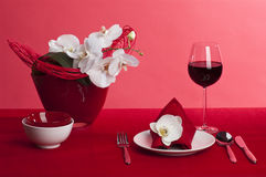 Table setting with orchid flowers. Table setting with white orchid flowers on red tablecloth on red background royalty free stock image