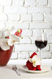 Table setting with orchid flowers. Table setting with white orchid flowers on white tablecloth on brick wall background royalty free stock images