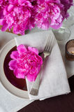 Table setting with pink peonies, vintage cutlery and brown table Royalty Free Stock Image