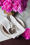 Table setting with pink peonies, vintage cutlery and brown table Stock Photo