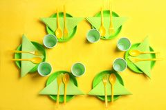 Table setting with plastic dishware on color background. Top view royalty free stock photography