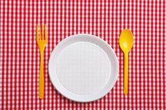 Table setting with plastic dishware on plaid fabric. Flat lay stock photography