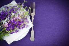 Table setting with purple flowers. Festive table setting, plate, fork and a bouquet of flowers on purple background Royalty Free Stock Image