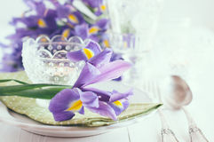 Table setting with purple iris flowers Stock Photos
