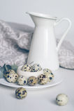 Table setting with quail eggs on a white plate, jug, linen napkin, green twig. Table setting with white plate and jug, green twig, linen napkin and quail eggs Royalty Free Stock Photos