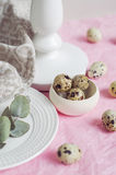 Table setting with quail eggs on a white plate, linen napkin, green twig. Table setting with white plate, linen napkin, green twig and quail eggs on a pink Stock Photo
