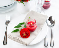 Table setting with red buttercup flowers. Festive dining table setting with red buttercup flowers, candles, napkins and shiny new cutlery in white Stock Photos