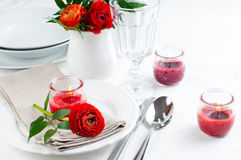 Table setting with red buttercup flowers. Festive dining table setting with red buttercup flowers, candles, napkins and shiny new cutlery in white Royalty Free Stock Photos