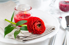 Table setting with red buttercup flowers Royalty Free Stock Images