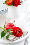 Table setting with red buttercup flowers Stock Photo