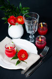 Table setting with red buttercups on a black background. Festive dining table setting with red buttercup flowers, candles, napkins and shiny new cutlery on a Royalty Free Stock Photography