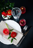 Table setting with red buttercups on a black background. Festive dining table setting with red buttercup flowers, candles, napkins and shiny new cutlery on a Stock Photo