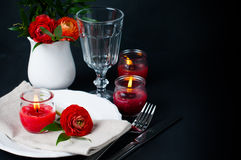 Table setting with red buttercups on a black background Stock Photos