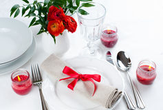 Table setting with red flowers. Festive dining table setting with red flowers, candles and ribbons in white tones Stock Images