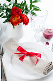 Table setting with red flowers. Festive dining table setting with red flowers, candles and ribbons in white tones Stock Photo