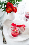 Table setting with red flowers. Festive dining table setting with red flowers, candles and ribbons in white tones Royalty Free Stock Photo