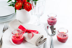 Table setting with red flowers. Festive dining table setting with red flowers, candles and ribbons in white tones Stock Photography