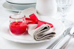 Table setting with red flowers. Festive dining table setting with red flowers, candles and ribbons in white tones Royalty Free Stock Images
