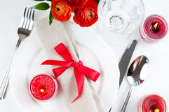 Table setting with red flowers. Festive dining table setting with red flowers, candles and ribbons in white tones Stock Image
