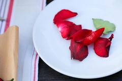 Rose petals on plate. Table setting with red rose petals on a white plate Royalty Free Stock Photos