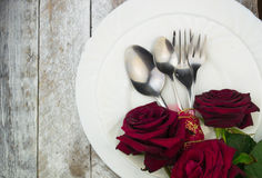 Table setting with red roses on white wood background Royalty Free Stock Photo
