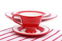 Red tea cup and saucer on a striped napkin Royalty Free Stock Image