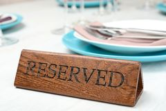 Table setting with RESERVED sign in restaurant. Closeup royalty free stock images