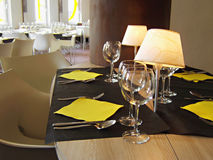Table setting in restaurant. Table setting in a restaurant with yellow napkins, silverware, black tablecloth and small lamps Royalty Free Stock Photos
