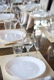 Table setting in the restaurant, including glasses for wine, champagne and cognac, napkins and plates for guests. Table setting in the restaurant, including royalty free stock photo