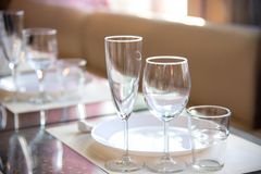 Table setting in the restaurant, including glasses for wine, champagne and cognac, napkins and plates for guests. Table setting in the restaurant, including royalty free stock photography
