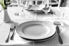 Table setting in restaurant interior, desaturated. Lunch table set in restaurant interior, cutlery Royalty Free Stock Image
