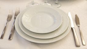 Table setting in a restaurant. Plates, forks and knives on a white tablecloth. Copy space royalty free stock photo