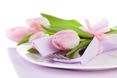 Table setting with roses tulips and cutlery Stock Photo