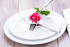 Table setting with a single pink rose Stock Images