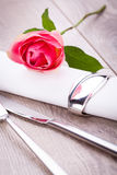 Table setting with a single pink rose Stock Photo