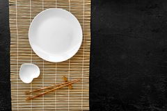 Table setting for sushi roll. Empty plate on mat near chopstick and bowl for sause on black table top view copyspace Stock Photography