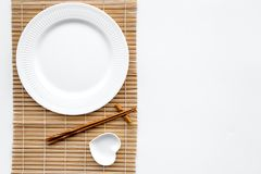 Table setting for sushi roll. Empty plate on mat near chopstick and bowl for sause on white background top view Stock Photography