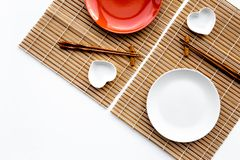 Table setting for sushi roll. Empty plate on mat near chopstick and bowl for sause on white background top view Royalty Free Stock Photos