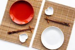 Table setting for sushi roll. Empty plate on mat near chopstick and bowl for sause on white background top view Stock Image