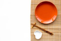 Table setting for sushi roll. Empty plate on mat near chopstick and bowl for sause on white background top view Stock Photos