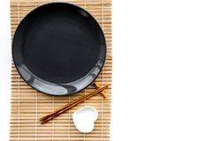 Table setting for sushi roll. Empty plate on mat near chopstick and bowl for sause on white background top view royalty free stock photography