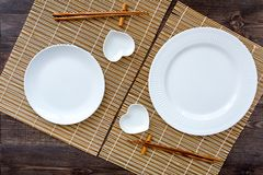 Table setting for sushi roll. Empty plate on mat near chopstick and bowl for sause on wooden table top view stock photography