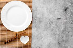 Table setting for sushi roll. Empty plate on mat near chopstick and bowl for sause on grey table top view copyspace Royalty Free Stock Photography
