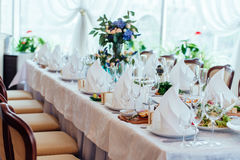 Table setting. Table served for wedding banquet, close up view. White napkin on a white empty plate on dining table Stock Image