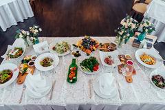 Table setting. Table served for wedding banquet. White napkin on a white empty plate on dining table Royalty Free Stock Images