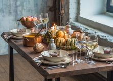 Table setting for Thanksgiving. Autumn table with pumpkins and candles in the center and a personal compliment. In the form of a jar of jam royalty free stock photography