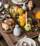 Table setting for Thanksgiving. Autumn table with pumpkins and candles in the center stock images
