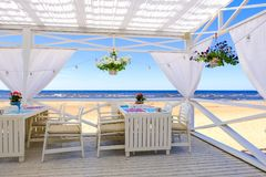 Restaurant on the beach. Table setting at tropical beach restaurant, sea royalty free stock photography