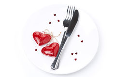 Table setting for Valentine's Day with fork, knife and hearts. On white, top view Stock Photo